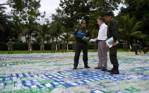El presidente de Colombia, Juan Manuel Santos, y dos agentes sobre las más de 12 toneladas de cocaína incautada.