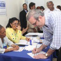 Luis Abinader firma documentación mientras vota